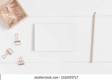 Top view of a white card mockup with workspace accessories on a white table.