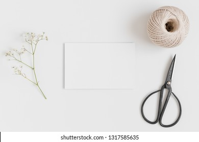 Top view of a white card mockup with a gypsophila and workspace accessories on a white table.