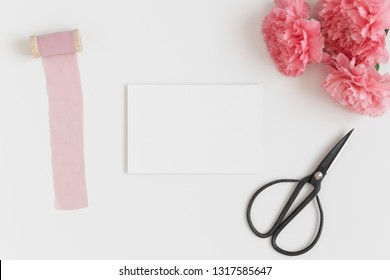 Top view of a white card mockup with a bouquet of pink carnations and workspace accessories on a white table.
