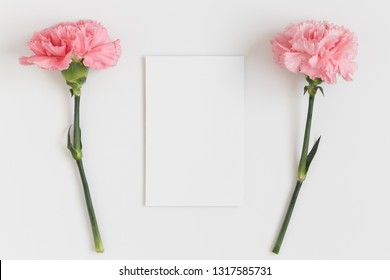 Top view of a white card mockup with pink carnations on a white table.