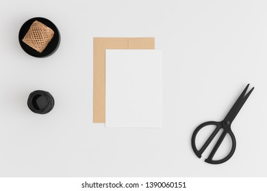 Top view of a white card mockup and envelope with workspace accessories on a white table.