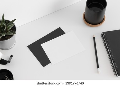 Top view of a white card mockup and envelope with a succulent plant, cup of coffee and workspace accessories on a white table.