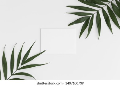 Top view of a white card mockup with palm leaf decoration on a white table.