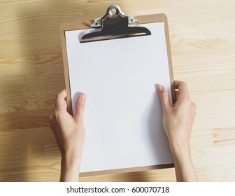 top view of white caucasian woman's hands holds clipboard with blank white paper sheet over wooden table