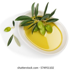 Top view of white ceramic bowl with olive oil and twig with green olive fruits isolated on white background.