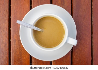 Top view of white ceramic cup with saucer and silver teaspoon of coffee on wooden table in garden It is a drink for refreshment.