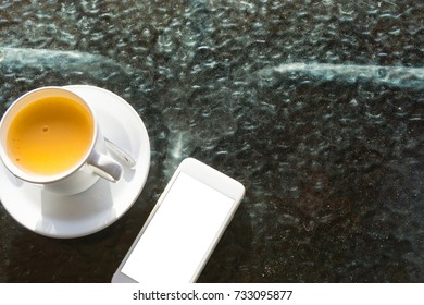 Top view of white ceramic tea cup with thai milktea inside and blank white screen smartphone on the glass table.