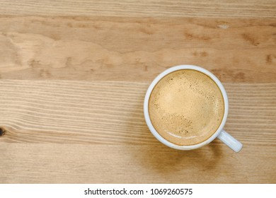 Top view of white coffee cup filled with fresh hot espresso on wooden background