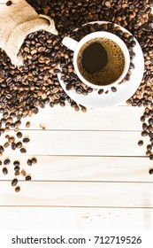 top view white coffee cup and coffee beans on wood floor background.