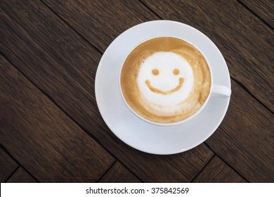 Top view white cup of latte art happy smile face on brown wooden table background with copyspace.