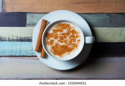 Top view white cup of salep milky hot drink of Turkey with cinnamon sticks and powder on wooden backdrop