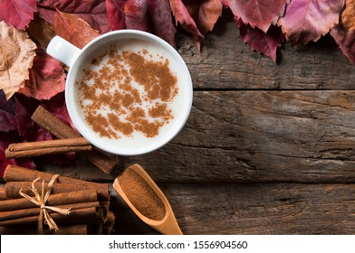 Top view white cup of salep milky hot drink of Turkey with cinnamon sticks, powder and autumn leaves on wooden backdrop