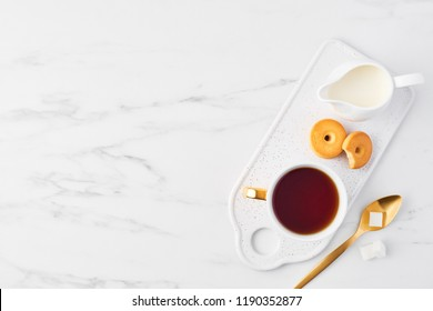 Top view of white cup of tea, biscuits and milk jug on serving plate, golden spoon with sugar cubes on white marble background. Flat lay with copy space.
