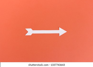Top view of white cutout paper arrow pointing on side on orange background