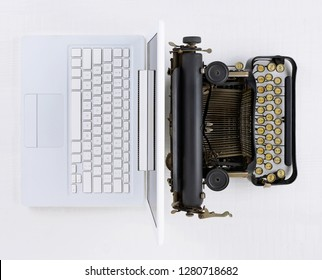 Top view of a white desk with old fashioned typewriter back-to-back with a modern laptop computer.