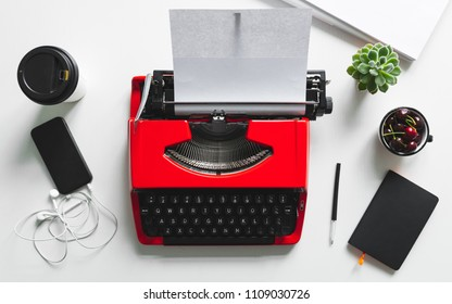 Top view of white desk workplace with bright red vintage typewriter