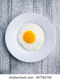 Top view of white dish with fried egg on wooden background.