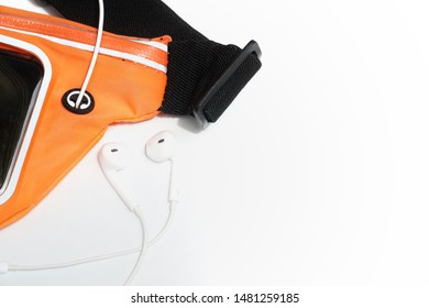 Top view of white earphone, mobile phone and waterproof sport running belt. Healthy, Exercise, Fitness and Technology concept.
