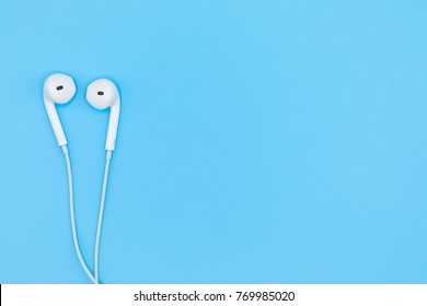 Top view of White Earphones on Blue plastic texture background. Pastel color concept, Minimal concept. Copy space. Music is my life concept