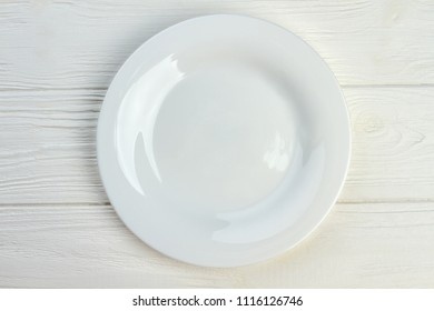 Top view of white empty plate. Ceramic plate on white wooden background.