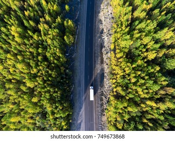 Top view at white freight truck driving between rock tunnel in golden autumn forest of Karelia, Russia