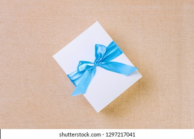 Top view of white gift box tied by blue ribbon