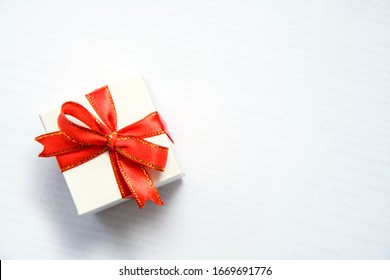 Top view of white gift box with red ribbons isolated on white background. Shopping concept boxing day and black Friday sale composition.