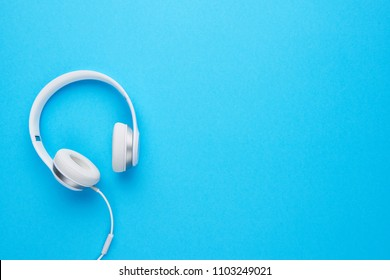 Top view of white headphones on blue background with copy space. Flat lay.
