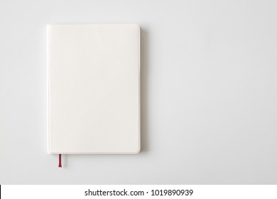 Top view of white leather notebook on white desk background with copy space.