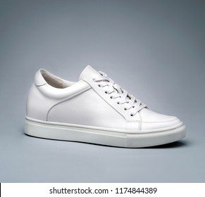 Top view of white leather shoe in front of gray gradient background. Concept of casual clothes.