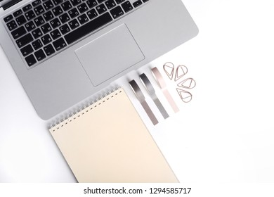 Top view of white office desk with laptop and notebook. Top view with copy space