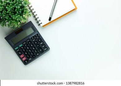 Top view of white office desk with calculator,notepad. Top view with copy space