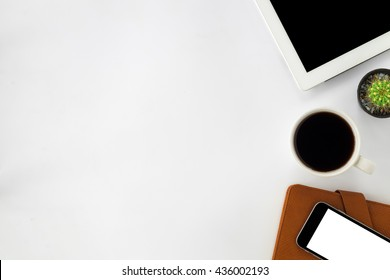 Top view of white office desk with blank screen tablet,leather notebook,smart phone and cup of coffee.top view with copy space.Office supplies and gadgets on desk table.Working desk table concept.