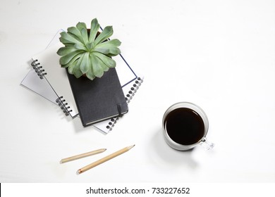 Top view of white office desktop with plant, coffee cup, glasses and stationery items. Mock up