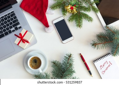 Top View of white Office Table with cropped Laptop electronic Gadgets and Christmas Theme Items