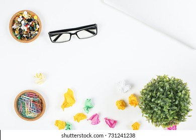 Top view of white office table with laptop, glasses, supplies and decorative plant. Creative designer desktop