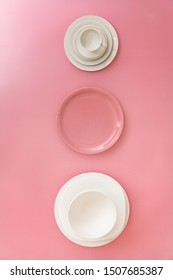Top view of white and pink dish ware against colorful background.