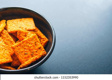 Top view of a white plate filled with flatbread crackers on a black desk.Spring day. Copy space for text.