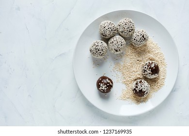 Top view of white plate with preparing energy ball in sesame seeds
