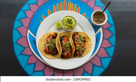 Top view of a white plate with three Mexican tacos of meat accompanied with small pot of guacamole and spicy sauce on a wooden table with various colors