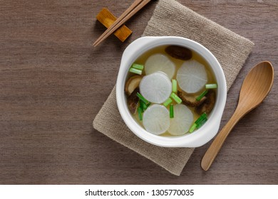 top view of white radish clear soup in a ceramic bowl on wooden table. asian homemade style food concept.