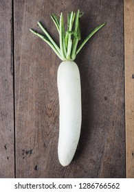 Top view of white radish on wooden table.