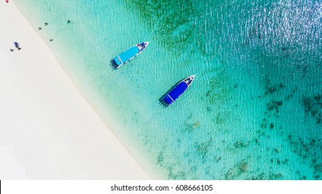 Top view of white sand beach with power speed boat on the emerald green sea, Ta Fook island, south of Myanmar, Top view from drone