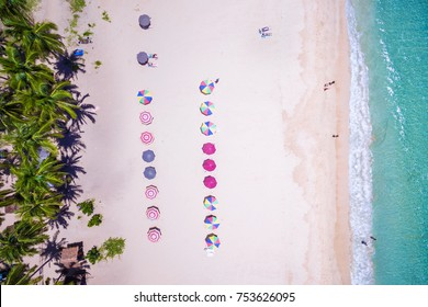 Top view of white sand beach with colourful umbrellas and people bathing in El Nido, Palawan, Philippines.