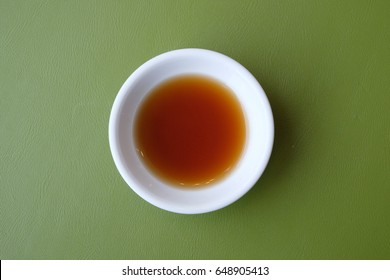 Top view of white soy sauce on white bowl serve on green table background with copy blank space