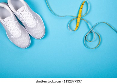 Top view of white sport shoes (sneakers) with measuring tape on cyan blue background. Losing weight and sport concept with copy space. Flat Lay.