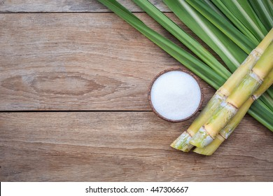 Top view white sugar and sugar cane and leaf on wooden background