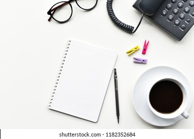 Top view white table, Blank white book and pencil silver for business notes in free time or holiday have desktop phone communicate and glasses,black coffee,paper clip is an element with copy space