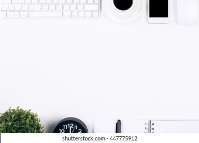 Top view of white table with various office tools, electronic devices and decorative items. Mock up