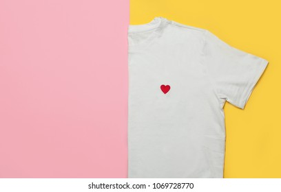 Top view of white woman t-shirt on pink and yellow background. Fashion clothes set. Flat lay. Place for text. 90's style.